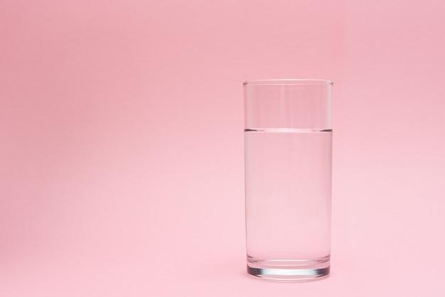 Glas wasser auf rosa hintergrund