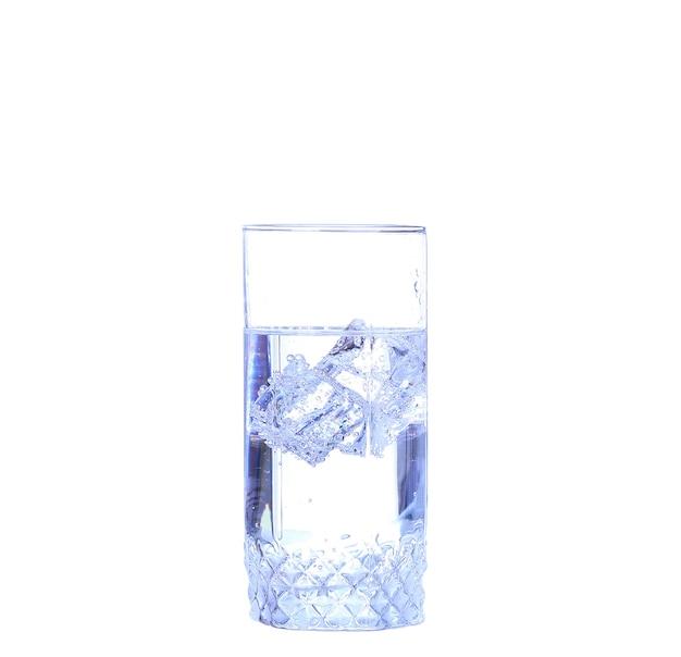 Glas wasser, eis und frische zitronenscheibe an einer weißen wand