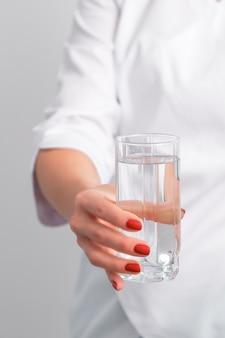 Glas wasser in weiblicher hand