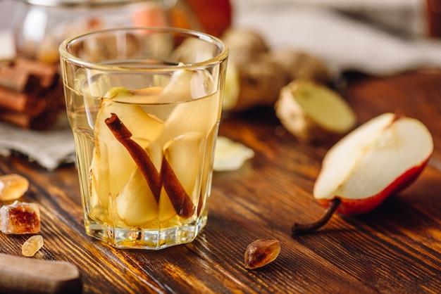Glas wasser mit birne, zimtstange, ingwerwurzel und etwas zucker. zutaten auf holztisch verstreut.