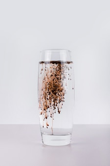 Glas wasser mit dunkler flüssigkeit auf weißer wand.