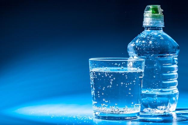 Glas wasser mit einer flasche auf tabelle