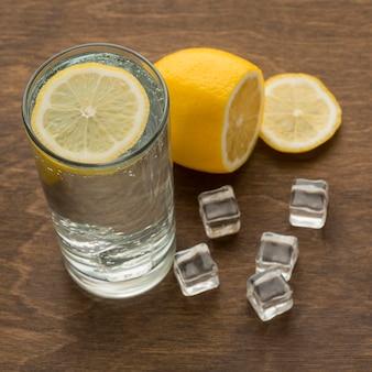 Glas wasser mit gesunder zitronenscheibe und eis