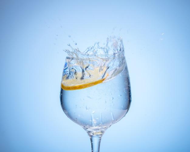 Glas wasser mit zitrone fiel ein und spritzte auf hellblauen farbverlaufshintergrund.