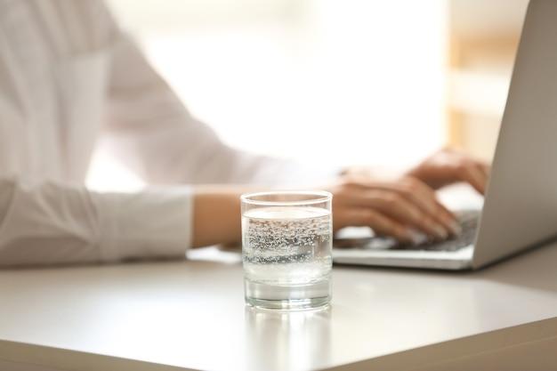 Glas wasser nahe frau, die am laptop am tisch arbeitet