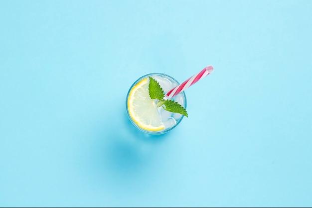 Glas wasser oder getränk mit eis, zitrone und minze auf blauem grund. konzept eines heißen sommers, alkohol, kühlendes getränk, durst stillend. flache lage, draufsicht
