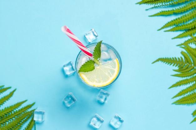 Glas wasser oder getränk mit eis, zitrone und minze auf blauem grund mit palmblättern und farn. eiswürfel. konzept von heißem sommer, alkohol, kühlendem getränk, durstlöschung, bar. flache lage, draufsicht