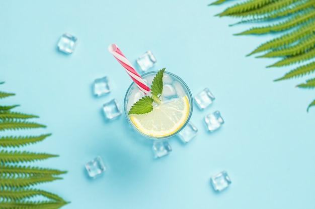 Glas wasser oder getränk mit eis, zitrone und minze auf einer blauen oberfläche mit palmblättern und farn. eiswürfel. konzept des heißen sommers, alkohol, kühlendes getränk, durstlöschung, bar. flachgelegt, draufsicht