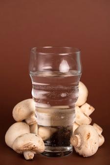 Glas wasser, umgeben von frischen pilzen