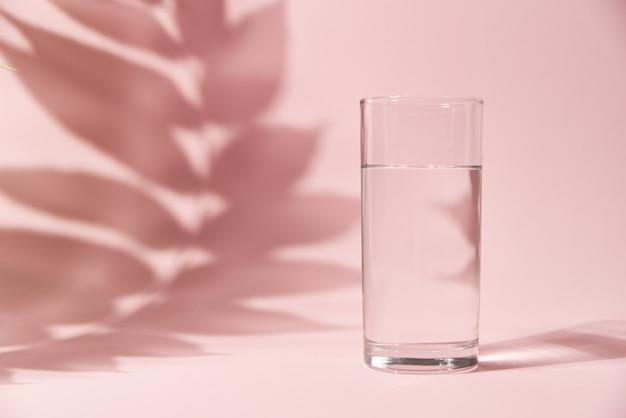 Glas wasser und blattschatten auf rosa hintergrund