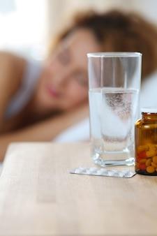 Glas wasser und drogen, die auf nachttisch vor der schlafenden frau stehen