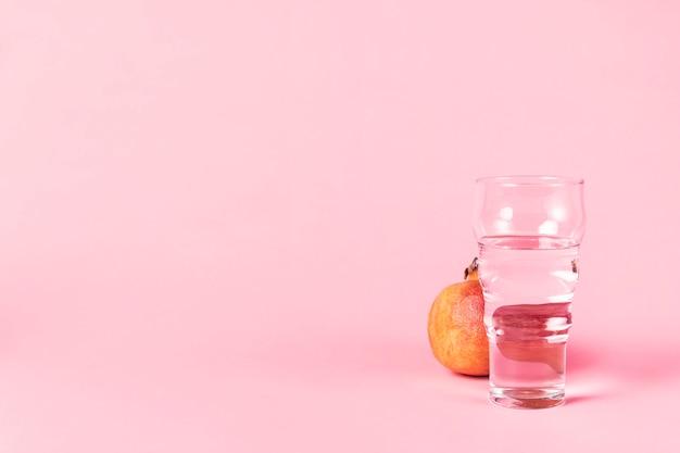 Glas wasser und granatapfelfrucht