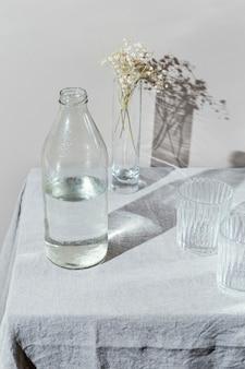 Glas wasser und vase mit blumen