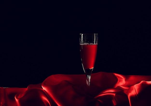 Glas wein auf roter seide mit dunkler oberfläche