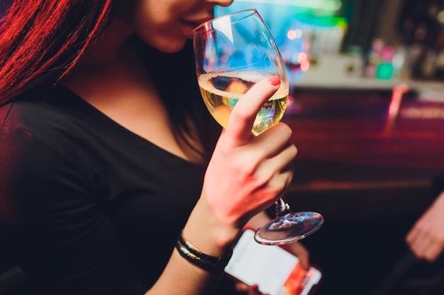 Glas wein in schönen weiblichen händen. großes glas gefüllt mit rotwein in gepflegten frauenhänden. konzept der romantik und feier.