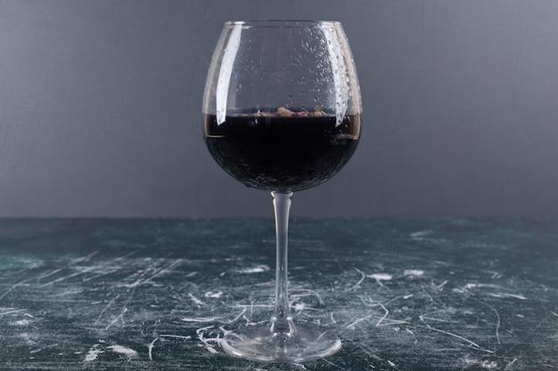 Glas wein mit eis auf blauem tisch.