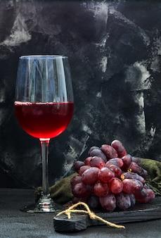 Glas wein mit trauben auf schwarzem holz