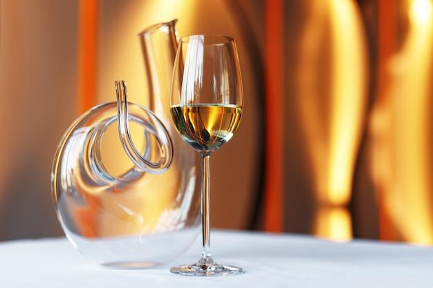 Glas wein und eine karaffe auf einem tisch mit einer weißen tischdecke.