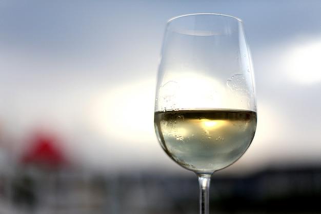 Glas weißwein auf dem himmelhintergrund