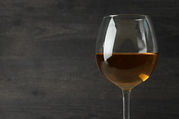 Glas weißwein auf dunklem holzhintergrund