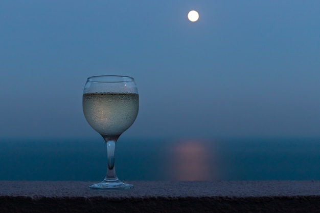 Glas weißwein auf einem balkon mit verschwommenem meer und vollmond