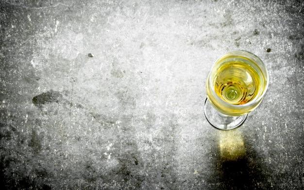 Glas weißwein auf steintisch.