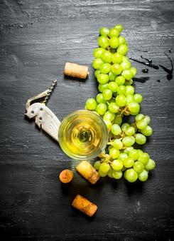 Glas weißwein mit korken und weintraube.