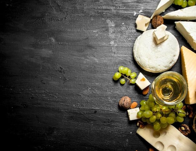 Glas weißwein mit verschiedenen käsesorten, trauben und nüssen. auf schwarzem holztisch.