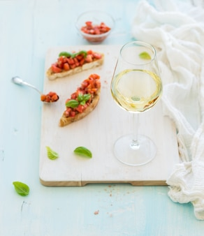 Glas weißwein-, tomaten- und basilikum bruschetta sandwich auf gemaltem hölzernem umhüllungsbrett