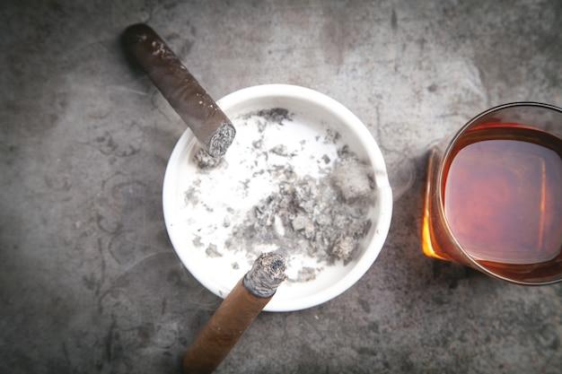 Glas whisky, aschenbecher und zigarren auf dem tisch.