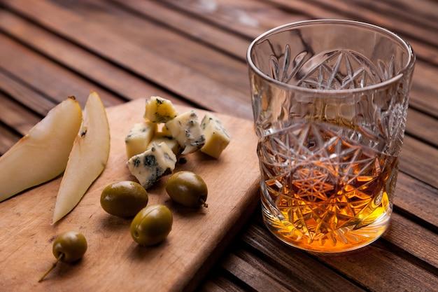 Glas whisky auf einem holztisch mit einem snack