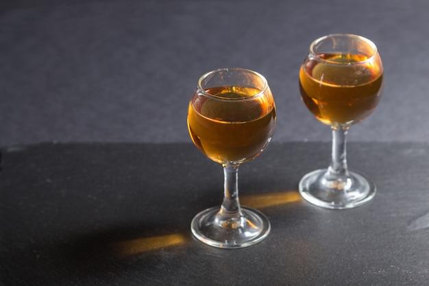 Glas whisky auf einem schwarzen steinschieferbrett auf schwarzer oberfläche. seitenansicht, kopierraum.