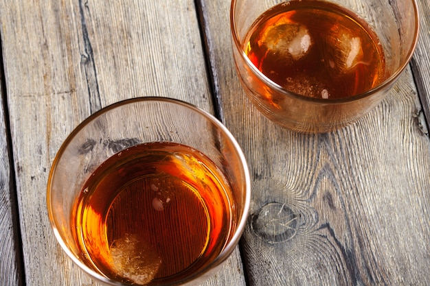 Glas whisky auf eis mit flasche auf hölzerner stange
