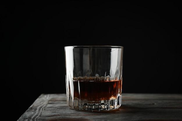 Glas whisky auf hölzernem hintergrund, raum für text