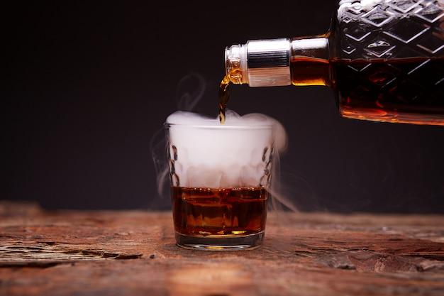 Glas whisky auf holztisch