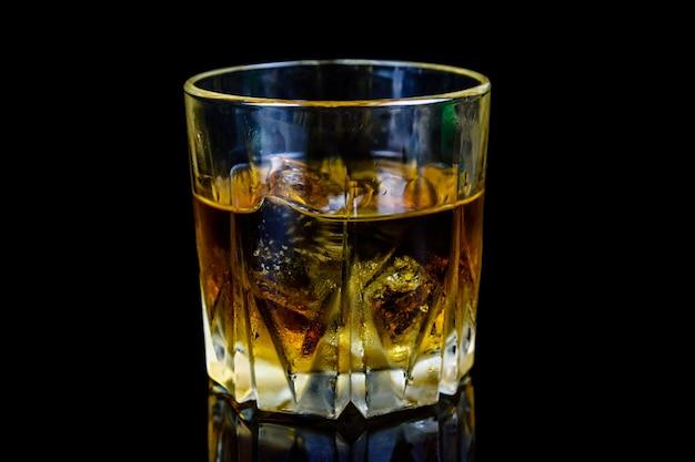 Glas whisky auf schwarzem hintergrund isoliert