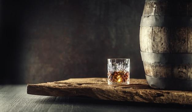 Glas whisky cognac oder bourbon in zierglas neben einem vinatge holzfass auf rustikalem holz und dunklem hintergrund.