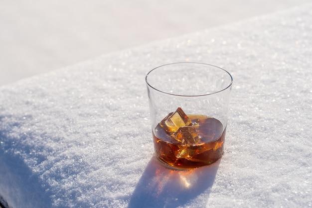 Glas whisky mit eis auf einem bett aus schnee und weißem hintergrund, nah oben. konzept des weihnachtswintermorgens