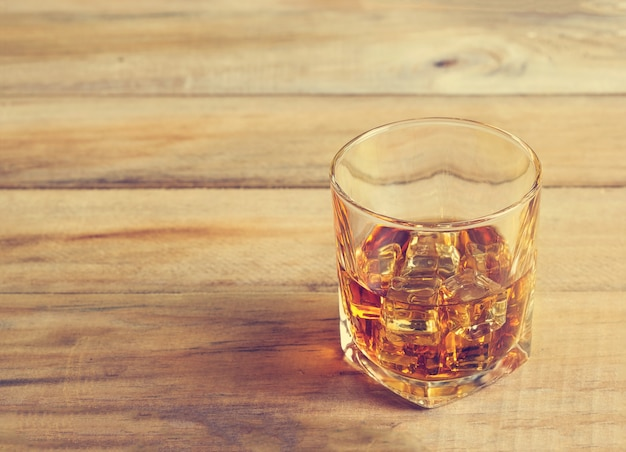 Glas whisky mit eis auf hölzernem hintergrund