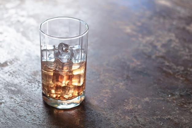Glas whisky mit eis auf schwarzem hintergrund