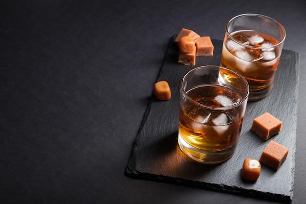 Glas whisky mit eis- und karamellbonbons auf einem schwarzen steinschieferbrett auf schwarzem hintergrund. seitenansicht, kopierraum, zurückhaltend.