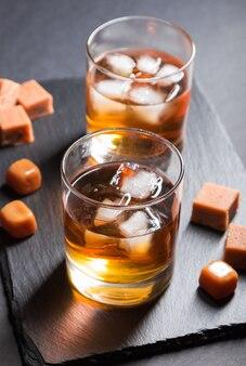 Glas whisky mit eis- und karamellbonbons auf einem schwarzen steinschieferbrett auf schwarzer oberfläche. seitenansicht, selektiver fokus.