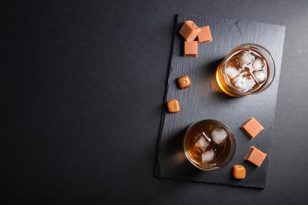 Glas whisky mit eis- und karamellsüßigkeiten auf einem schwarzen steinschieferbrett. draufsicht, kopie, raum