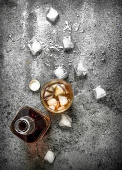 Glas whisky mit eiswürfeln. auf einem rustikalen hintergrund.