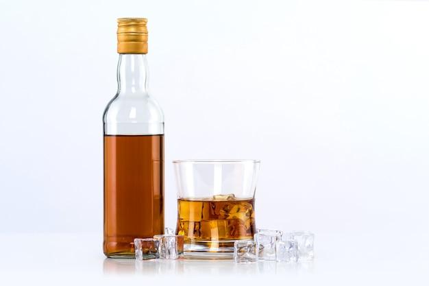 Glas whisky mit eiswürfeln und flasche auf weißer wand