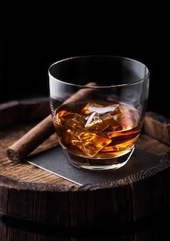 Glas whisky mit eiswürfeln und zigarre auf holzfass