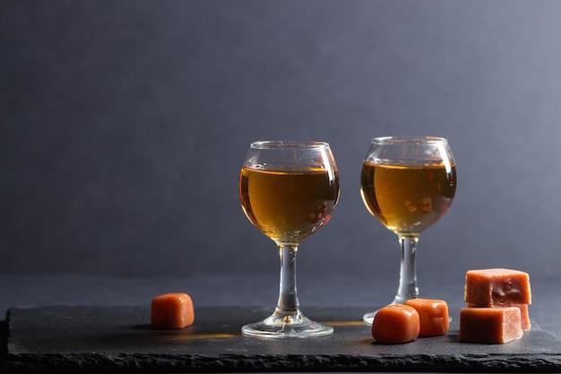 Glas whisky mit karamellbonbons auf einem schwarzen steinschieferbrett auf schwarzem hintergrund. seitenansicht, kopierraum.