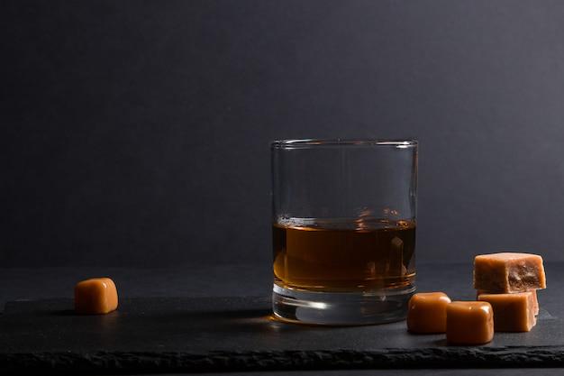 Glas whisky mit karamellbonbons auf einem schwarzen steinschieferbrett auf schwarzem hintergrund. seitenansicht, zurückhaltend, kopierraum.
