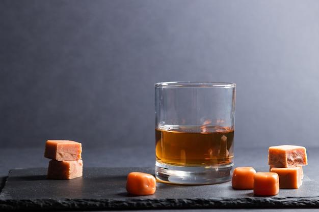 Glas whisky mit karamellbonbons auf einem schwarzen steinschieferbrett auf schwarzer oberfläche. seitenansicht, kopierraum.