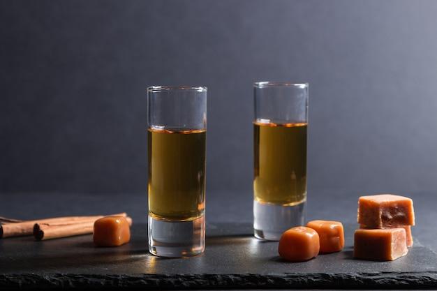 Glas whisky mit karamellbonbons auf einem schwarzen steinschieferbrett auf schwarzer oberfläche. seitenansicht.